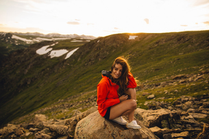 Woman sitting on rock looking at camera smiling, Rocky Mountain National Park, Colorado, USAの写真素材 [FYI03571058]
