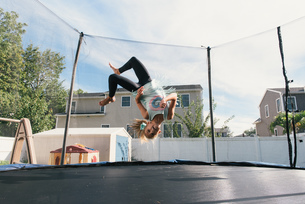 Girl upside down in mid air, jumping on trampolineの写真素材 [FYI03571131]