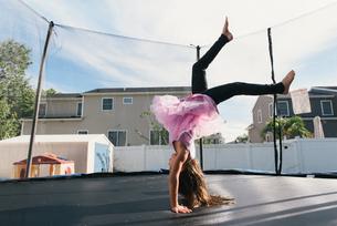 Girl upside down doing handstand on trampolineの写真素材 [FYI03571132]