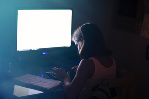 Girl using computer in dimly-lit roomの写真素材 [FYI03571347]