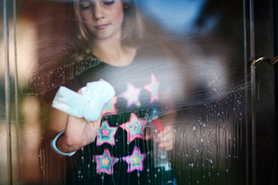 Girl cleaning glass doorの写真素材 [FYI03571367]