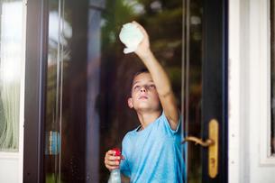 Boy reaching to clean glass doorの写真素材 [FYI03571368]