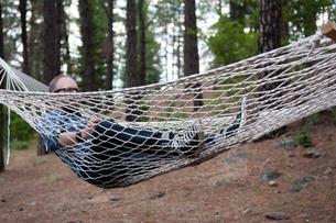 Man relaxing in hammock, Spokane, Washington, USAの写真素材 [FYI03571391]
