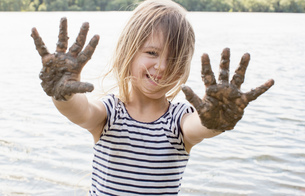 Portrait of girl with muddy hands in riverの写真素材 [FYI03571432]