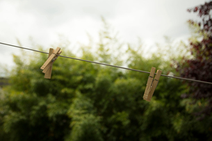Wooden clothes pegs on washing line, close-upの写真素材 [FYI03571472]