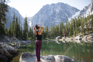 Young woman standing on rock beside lake, looking at view, The Enchantments, Alpine Lakes Wildernessの写真素材 [FYI03571536]