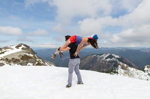 Man carrying woman over shoulder on mountain-top, Silver Star Mountain, Washington, USAの写真素材 [FYI03571551]