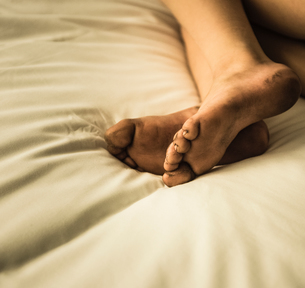 Cropped view of boys dirty bare feet on bedの写真素材 [FYI03571614]
