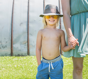 Boy wearing sunglasses and hat, holding mothers handの写真素材 [FYI03571619]