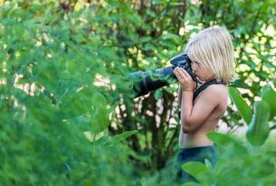 Boy in bush taking photographの写真素材 [FYI03571649]