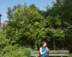 Woman sitting on park bench looking at smartphoneの写真素材 [FYI03571675]