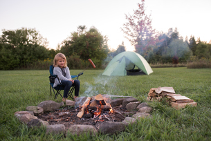 Young girl sitting beside campfire, cooking sausageの写真素材 [FYI03571704]