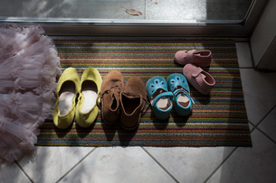 Different size shoes lined up on doormatの写真素材 [FYI03571706]