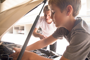 Boy learning car maintenance with father under car hoodの写真素材 [FYI03571767]