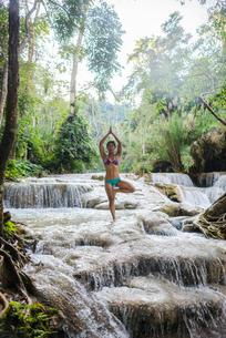 Woman standing on one leg, in tree pose, in Kuang Si waterfall, Luang Prabang, Laosの写真素材 [FYI03571786]