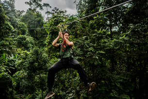Man on zip wire in forest, Ban Nongluang, Champassak province, Paksong, Laosの写真素材 [FYI03571801]