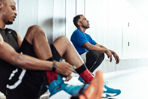 Exhausted male basketball players taking a break on changing room floorの写真素材 [FYI03571860]