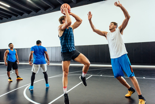 Male basketball player jumping with ball in basketball gameの写真素材 [FYI03571870]