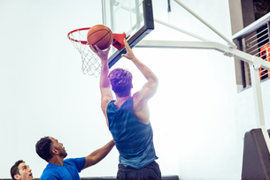 Male basketball player aiming ball for hoop in basketball gameの写真素材 [FYI03571874]