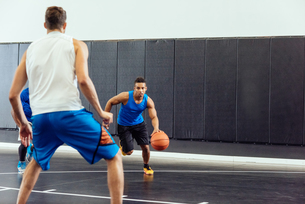 Male basketball player running with ball in basketball gameの写真素材 [FYI03571877]