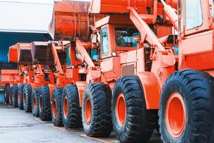 Row of parked red bull dozer trucksの写真素材 [FYI03571901]