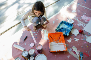 Girl in garage stirring paint in paint tinsの写真素材 [FYI03571920]