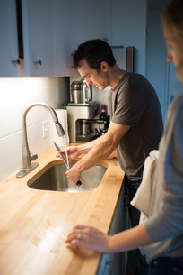 Mid adult couple washing kitchen knife at kitchen sinkの写真素材 [FYI03571943]