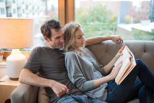 Mid adult couple reclining on sofa reading a bookの写真素材 [FYI03571944]