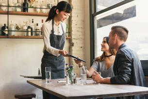 Waitress handing young couple bill in restaurantの写真素材 [FYI03571983]
