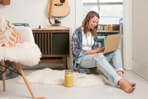 Woman sitting in living room using laptopの写真素材 [FYI03572045]