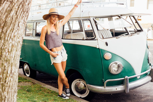 Woman by vintage camper van looking at cameraの写真素材 [FYI03572107]