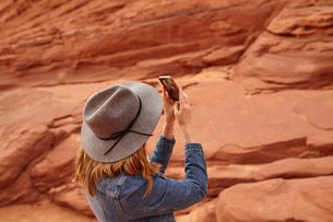 Woman taking photograph, using smartphone, Page, Arizona, USAの写真素材 [FYI03572110]