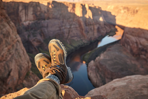 Man sitting on rock, close-up of feet, Page, Arizona, USAの写真素材 [FYI03572112]
