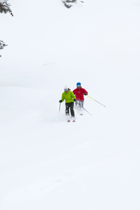 Two skiers, skiing downhill, low angle viewの写真素材 [FYI03572139]