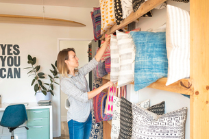 Female interior designer adjusting cushions on shelves in retail studioの写真素材 [FYI03572148]