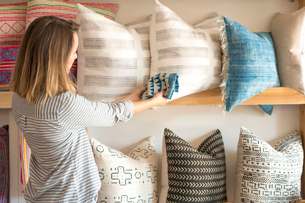 Rear view of female interior designer trying textile against cushions in retail studioの写真素材 [FYI03572149]