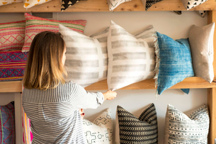 Rear view of female interior designer adjusting cushions on shelves in retail studioの写真素材 [FYI03572150]