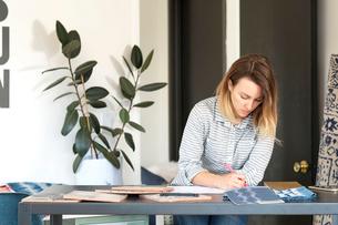 Female interior designer drawing designs at desk in retail studioの写真素材 [FYI03572151]