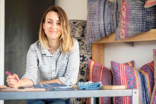 Portrait of female interior designer drawing designs at desk in retail studioの写真素材 [FYI03572152]