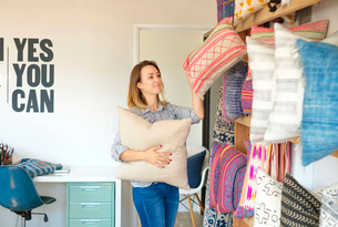 Female textile designer placing cushions on retail studio shelvesの写真素材 [FYI03572154]
