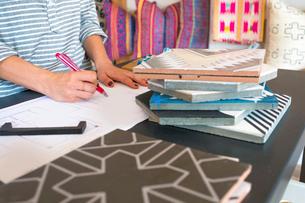 Mid section of female interior designer drawing designs at desk in retail studioの写真素材 [FYI03572155]