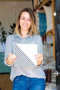 Portrait of female interior designer holding ceramic tile in retail studioの写真素材 [FYI03572156]