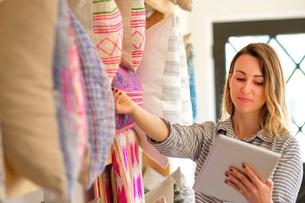 Female textile designer stocktaking cushions on retail studio shelvesの写真素材 [FYI03572157]