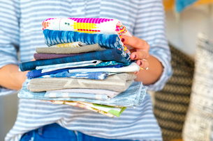 Mid section of female interior designer holding stack of textile swatches in retail studioの写真素材 [FYI03572158]