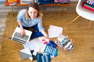 Overhead portrait of female interior designer using laptop on floor in retail studioの写真素材 [FYI03572159]