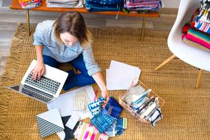 Overhead view of female interior designer using laptop on floor in retail studioの写真素材 [FYI03572160]
