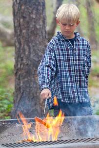 Boy barbecuing sausage on flaming grill in forest, Sedona, Arizona, USAの写真素材 [FYI03572177]