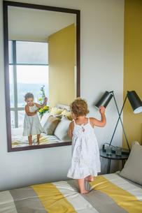 Girl dancing in front of mirror in bedroomの写真素材 [FYI03572481]