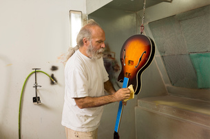 Guitar maker in workshop using cloth to varnish guitarの写真素材 [FYI03572532]