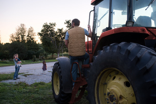 Family on farm, father climbing into tractorの写真素材 [FYI03572579]